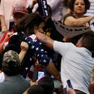Protester Bryan Sanders, centre left, is punched by a Trump supporter as he is escorted out of Republican presidential candidate Donald Trump's rally at the Tucson Arena in Arizona (left). Photo: Mike Christy/Arizona Daily Star via AP