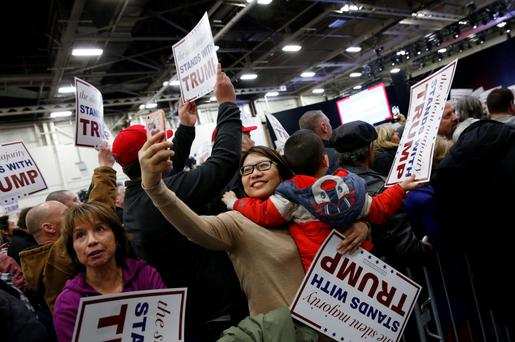 Supporters of US Republican presidential candidate Donald Trump hold signs during a campaign event at Grumman Studios in Bethpage, New York