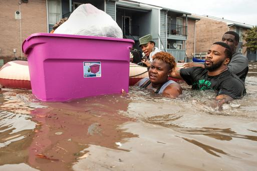 Residents evacuate their flooded apartment complex in the Greenspoint area of Houston. Photo: Brett Coomer/Houston Chronicle/AP