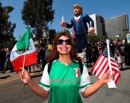 A protester poses in front of a giant effigy of Donald Trump on May Day in Los Angeles, California. Photo: Getty Images