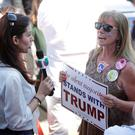 A TV reporter interviews a Trump supporter during a campaign stop for the US Republican presidential candidate in Lynden, Washington. Below: A young Donald Trump supporter at a campaign rally in Spokane, Washington. Photos: Getty/Reuters