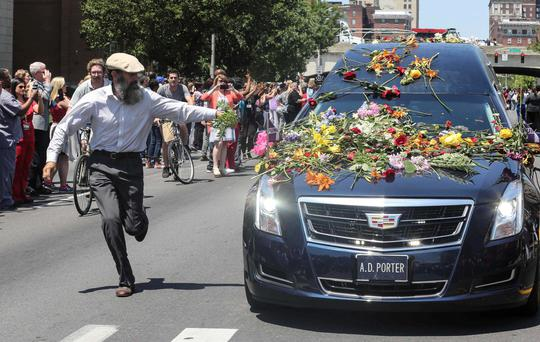 A man reaches out to touch the hearse carrying the body of Muhammad Ali with flowers as it drives down Broadway toward Cave Hill Cemetery in Louisville, Kentucky