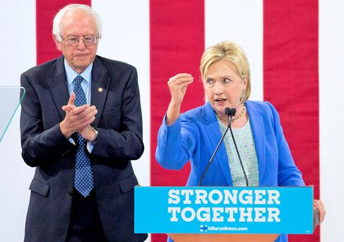 Presumptive Democratic presidential candidate Hillary Clinton speaks at a rally in New Hampshire as Bernie Sanders applauds Photo: AFP/Getty Images