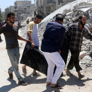 Men carry a dead body after an air strike on the rebel-held Al-Hilwaniyeh neighbourhood in Aleppo, Syria, yesterday. Photos: Reuters
