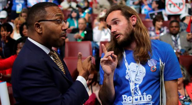 Delegate Chris Davis of Centennial, CO and supporter of Bernie Sanders speaks with Sen. Wesley Bishop of New Orleans and Hillary Clinton supporter