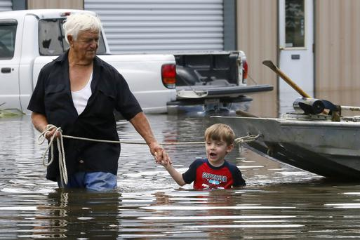 Richard Rossi and his grandson wade through water after their home was flooded in St Amant, Louisiana. Photo: Reuters