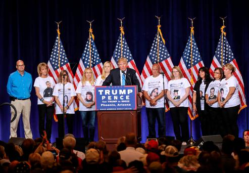 Republican presidential nominee Donald Trump stands on stage in Phoenix, Arizona, with parents who have lost family members, killed by undocumented immigrants