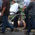 Ahmad Khan Rahami lies wounded on the ground surrounded by police after the shooting in Linden, New Jersey. Photo: AP