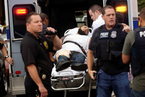 The suspect is tended to by medics as he's taken into custody on a stretcher. Photo: AP