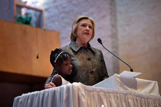 Hillary Clinton stands with Zianna Oliphant (9) while speaking during a Sunday service at Little Rock AMC Zion Church in Charlotte, North Carolina. Photo: Getty Images