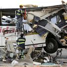 Workers cut away debris from the front of a bus involved in the crash on Interstate 10 near Palm Springs Photo: Reuters