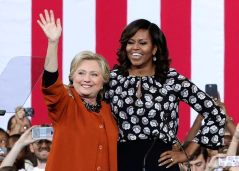 Democratic presidential candidate Hillary Clinton, left, and US first lady Michelle Obama, right, greet supporters during a campaign event at the Lawrence Joel Veterans Memorial Coliseum in Winston-Salem, North Carolina. Photo: Alex Wong/Getty Images