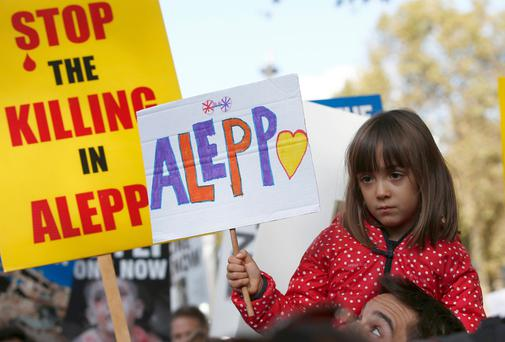 A child holds a placard during a demonstration urging the British government to intervene in the bombing of Aleppo, outside Downing Street, London