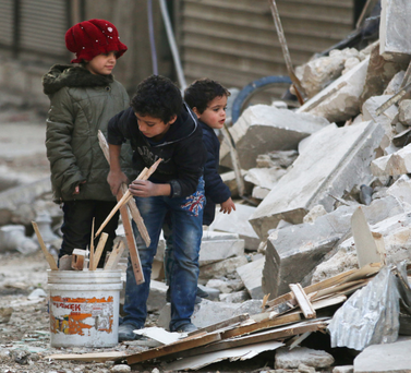 Children collect firewood at a site hit by airstrikes in the rebel held al-Shaar neighbourhood of Aleppo Photo: Reuters