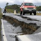 Traffic negotiates a road damaged by the quake at Chadmo, on Chiloé Island in southern Chile. Photo: Reuters