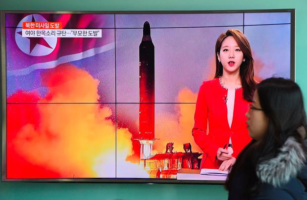 A woman walks past a TV screen at a railway station in Seoul showing footage of North Korea's missile launch. Photo: Getty Images