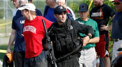 A US police officer escorts Republican members from the scene after a gunman opened fire during a baseball practice. Photo: Reuters