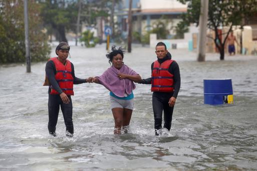 Rescue personnel help a woman through floods after the passing of Hurricane Irma in Havana, Cuba. Photo: Reuters