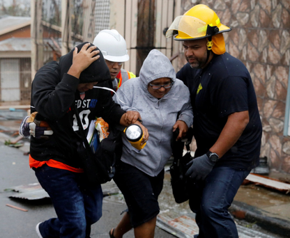 Rescue workers help people to shelters after the area was hit by Hurricane Maria in Guayama, Puerto Rico. Photo: Reuters