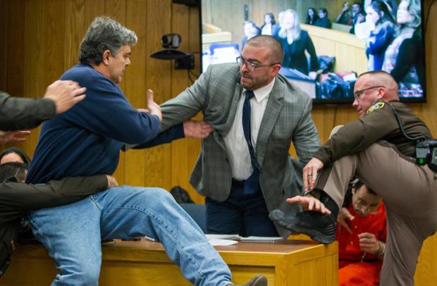 Randall Margraves, the father of three victims of Larry Nassar, left, lunges at Nassar, bottom right, in Eaton County Circuit Court