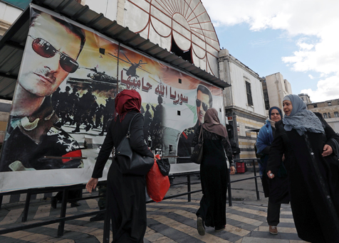 People walk next to a poster depicting Syria's President Bashar al-Assad in Damascus, Syria yesterday Photo: Reuters/Omar Sanadiki