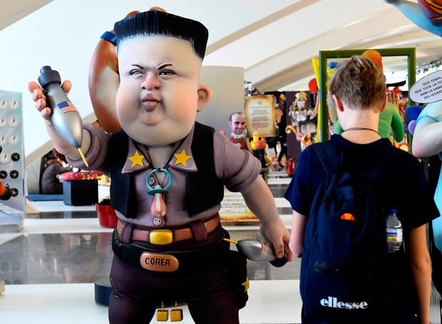 A boy looks at a Ninot, a doll depicting a celebrity that will be set alight during the Fallas festival, representing North Korean leader Kim Jong-Un in Valencia yesterday. Photo: Jose Jordan/Getty