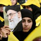 A woman carries a picture of Ayatollah Ali Khamenei at an event in the Bekaa Valley, Lebanon. Photo: Reuters/Hassan Abdallah