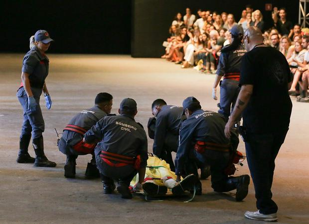 Tales Soares is taken from the catwalk by paramedics. Photo: AP
