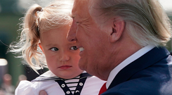 Not a good look: US President Donald Trump holds a little girl before departing the White House yesterday. Photo: Getty Images