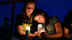 Pain: Melody Stout and Hannah Payan comfort each other during a vigil for the El Paso victims. Picture: PA