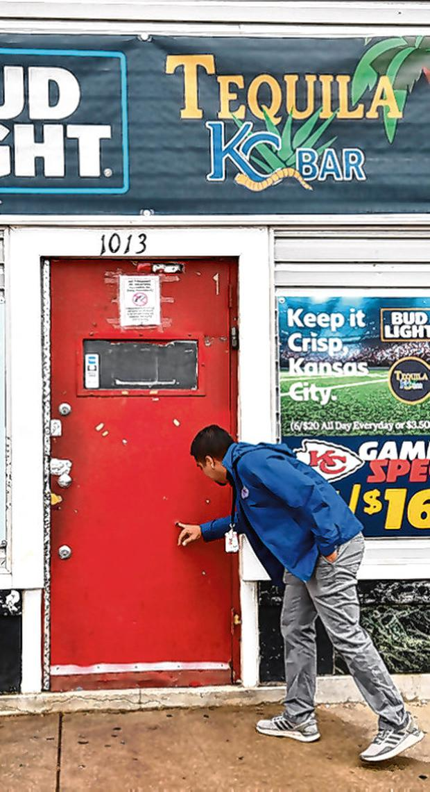 A man examines a bullet hole in the door of the Tequila KC Bar in Kansas City