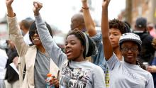 People celebrate as they gather in the streets of Baltimore, Maryland yesterday following the decision to charge six Baltimore police officers — including one with murder — in the death of Freddie Gray, a black man who was arrested and suffered a fatal neck injury while riding in a moving police van