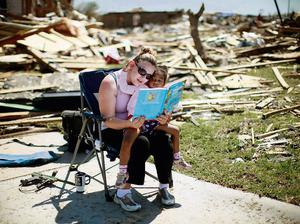REFILE - CORRECTING TYPO IN BOOK AUTHOR    Sarah Dick reads a Doctor Seuss book to her three-year-old daughter Jadyn at the driveway of her tornado-destroyed house in Oklahoma City, Oklahoma May 22, 2013. Rescue workers with sniffer dogs picked through the ruins on Wednesday to ensure no survivors remained buried after a deadly tornado left thousands homeless and trying to salvage what was left of their belongings.  REUTERS/Rick Wilking (UNITED STATES - Tags: DISASTER ENVIRONMENT)
