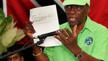 Jack Warner holds up a cheque during his Trinidad press conference.