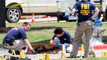 FBI investigators collect evidence, including a rifle, where two gunmen were shot dead after their bodies were removed in Garland, Texas.