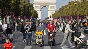 "People walk on the Champs Elysees during the ""day without cars"", in Paris. (AP)"