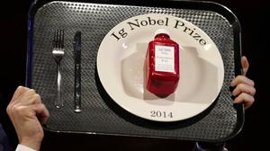 The 2014 Ig Nobel Prize trophy is hoisted high during the ceremony at Harvard University (AP)