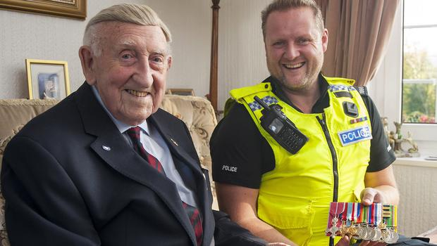D-Day veteran Colonel Alex Johnson and Pc Chris Cooke holding the veteran's medals that have been returned to him after two years (Northumbria Police/PA)