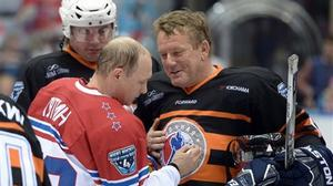 Russian president Vladimir Putin signs his autograph on a player's uniform after an exhibition hockey game at the Night Hockey League tournament in the Black Sea resort of Sochi (AP)