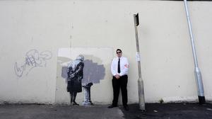A security guard stands next to a mural called Art Buff created by street artist Banksy which appeared in Folkestone