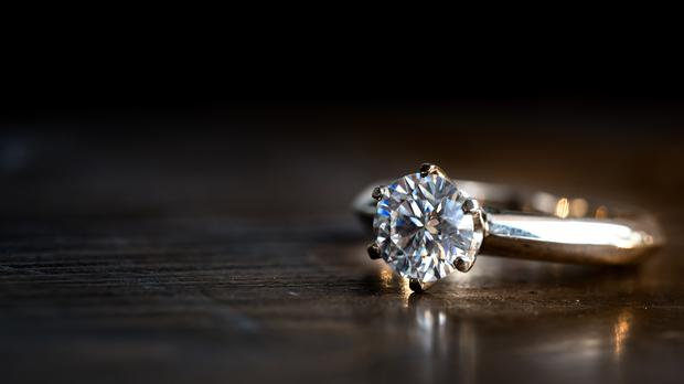 A diamond ring on a wooden table – (avagyanlevon/Getty Images)