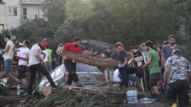People clean a flooded area in Tbilisi, Georgia (AP)