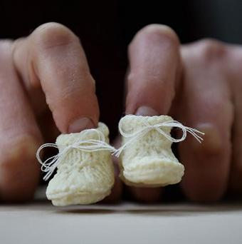 The one-inch long baby booties created using donated breast milk