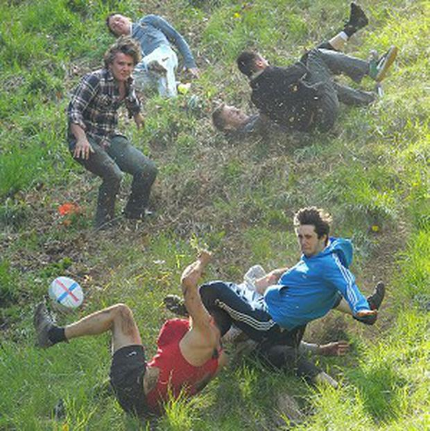 Competitors take part in the annual Cheese Rolling event at Coppers Hill near Brockworth, Gloucestershire