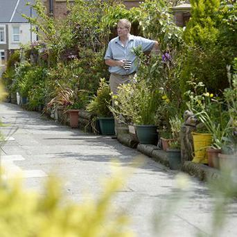 Resident Michael Kelley in Rockcliffe Avenue, Whitley Bay, North Tyneside, with flowerpots by the side of the street