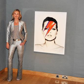 Model Kate Moss poses in front of works by Allen Jones (left) and Nick Knight (right), during a preview of Christie's forthcoming 'Kate Moss From The Collection of Gert Elfering' sale, which takes place on September 25th and will present a selection of works in various media celebrating Kate Moss.