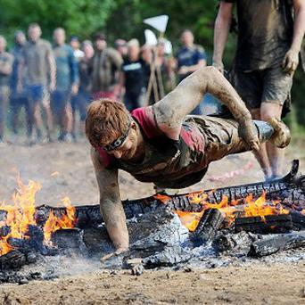 Lance Bombardier James Simpson, a double amputee, dives over a burning obstacle during the Spartan Race in Ripon, North Yorkshire.