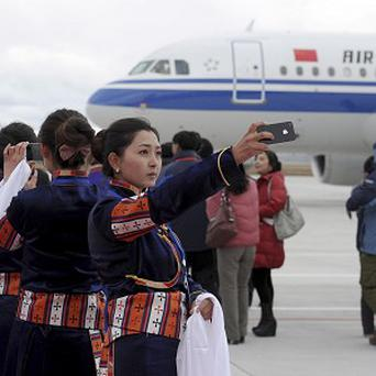 A Tibetan woman uses her mobile phone to take photos of a flight that touched down at Yading airport, the world's highest-altitude civilian airport (AP)
