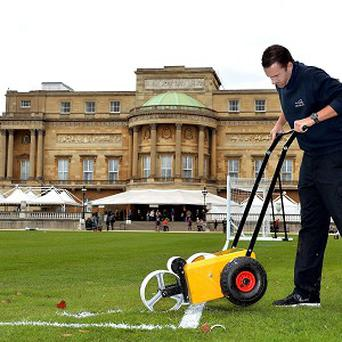 Karl Standley, a groundsman at Wembley Stadium, marks out the lines of a football pitch in the gardens of Buckingham Palace