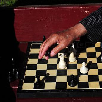 Dozens of people backed by a brass band are playing chess in downtown San Francisco to defy a recent crackdown by police